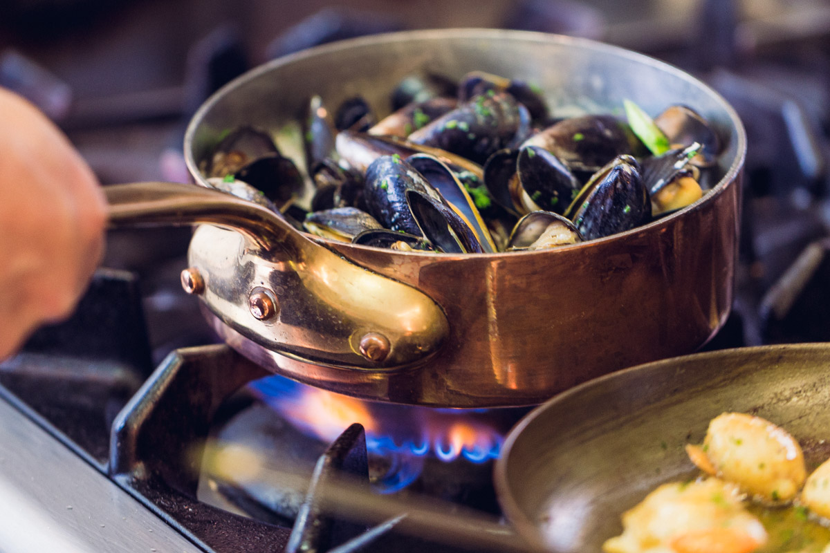Mussels cooking in a brass pan