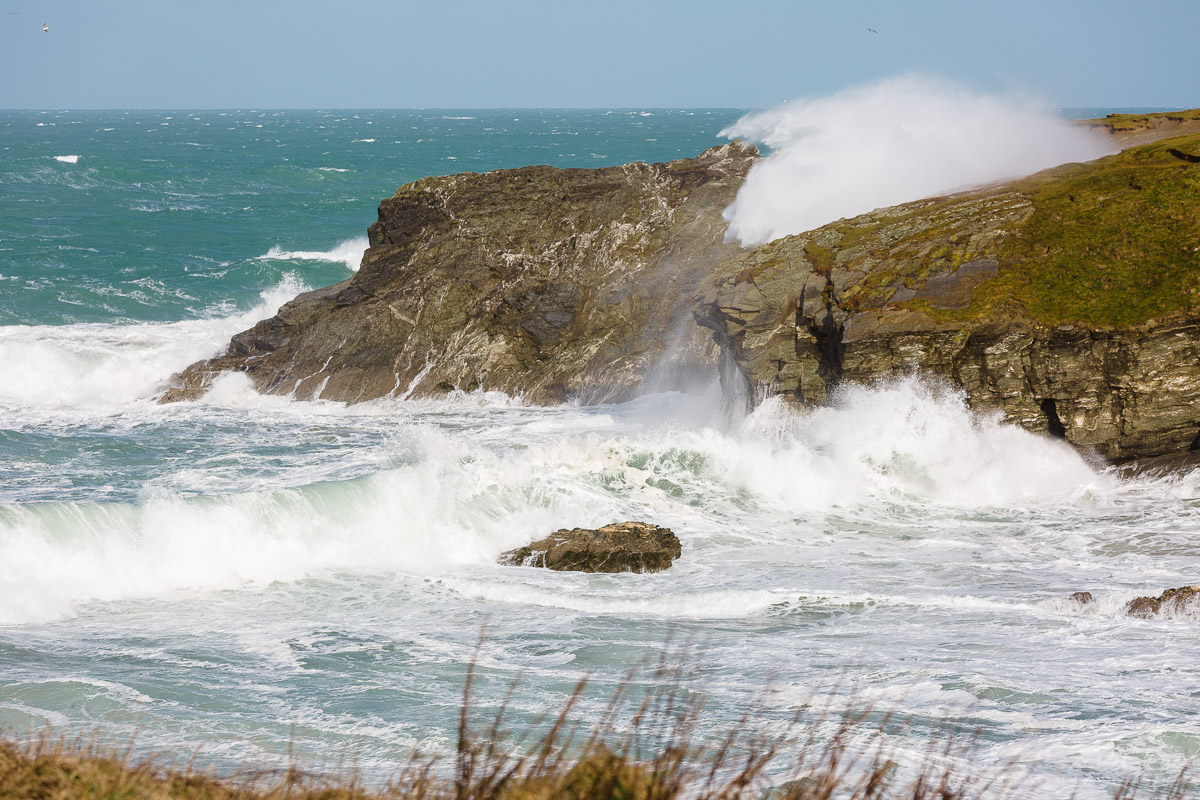wave crashes over headland in cornwall