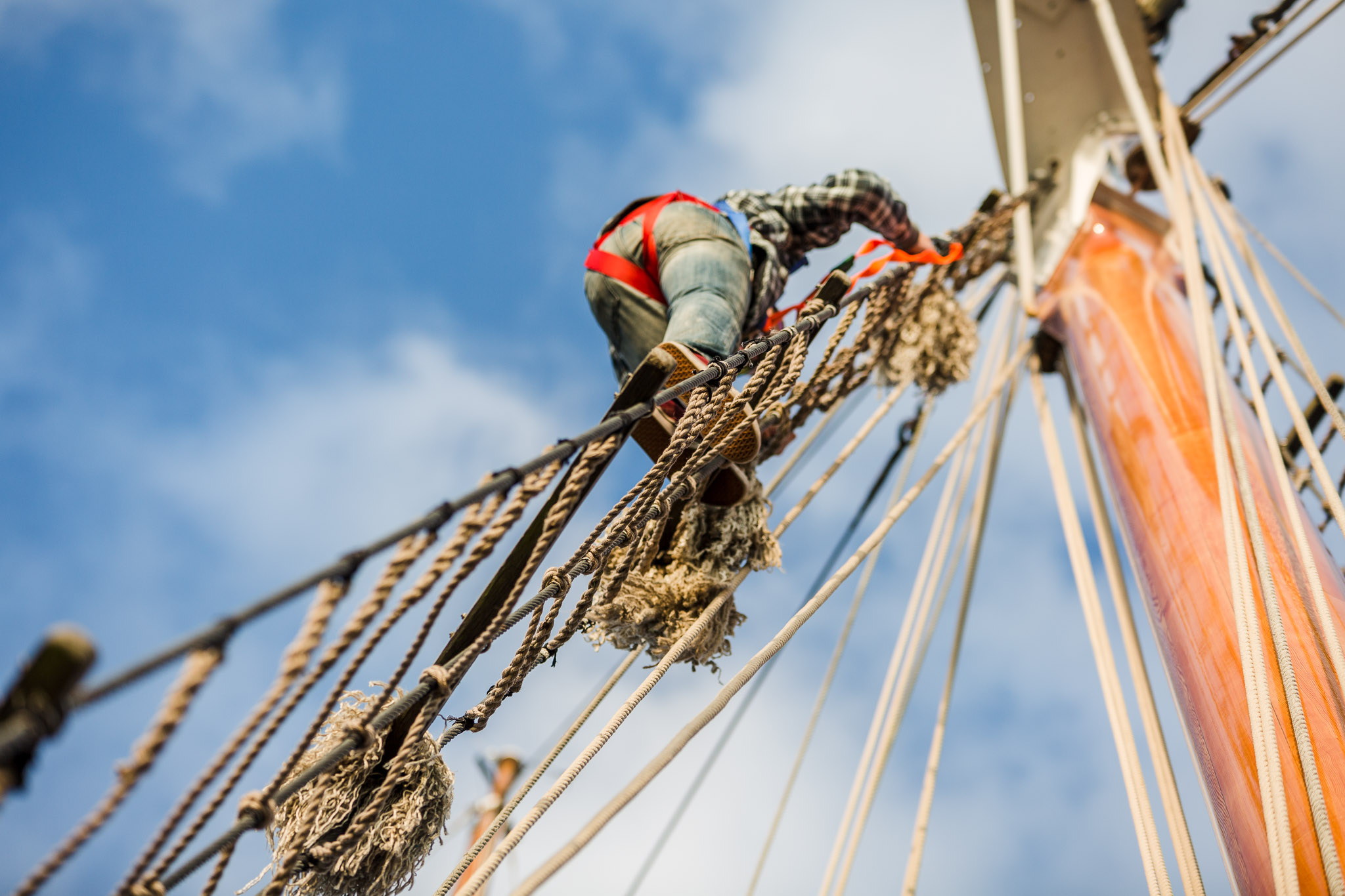 Climbing the rigging on a sailing boat in cornwall